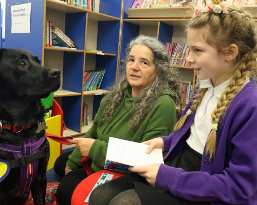 11 year old Amy reads to reading dog Lunar watched by owner Jane Baxter
