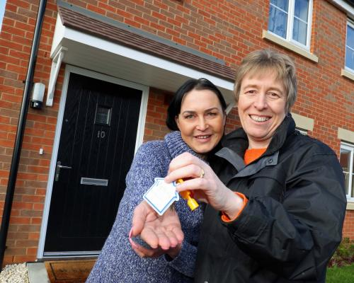 Christine Candlish right of Victory hands over the keys of her new home to Erika Krauzaite sm