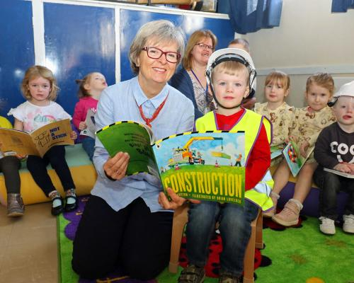 Maggie Abel of Abel Homes reads a book about construction with four year old Leyton at Little Acorns in Watton sm