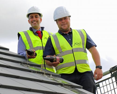 Paul LeGrice left and Danny Pinner top out the first new home at Abel Homes Bluebell Rise site in Bawdeswell sm