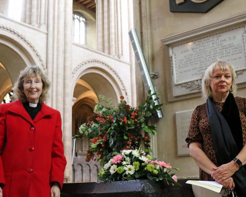 Rev Heather Knight left and Vision Norfolk chief executive Gina Dormer place flowers by the Thomas Tawell memorial in Norwich Cathedral sm