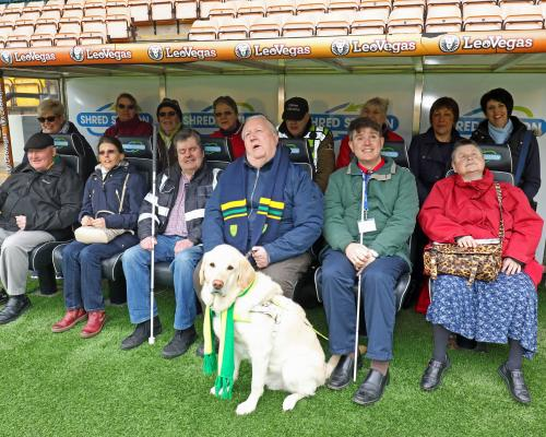 The group of visually impaired City fans from the NNAB testing out the dugout at Carrow Road sm
