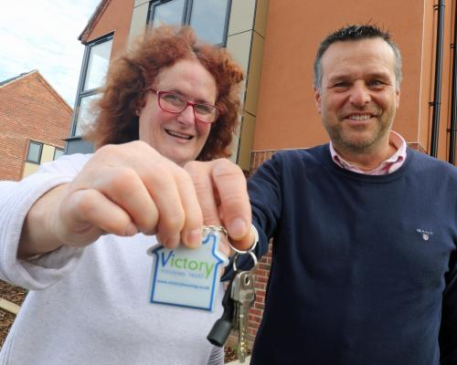 Victory Housing Trust development director Mark Burghall hands the keys to the 1000th new home to Jane Craske