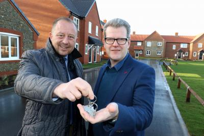 Paul Pitcher left of Wellington hands over the keys to new homes at Bacton to John Archibald of Victory Housing Trust sm
