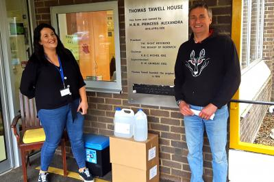Samantha Capper manager at Thomas Tawell House receives the hand sanitiser from Patrick Saunders of Black Shuck